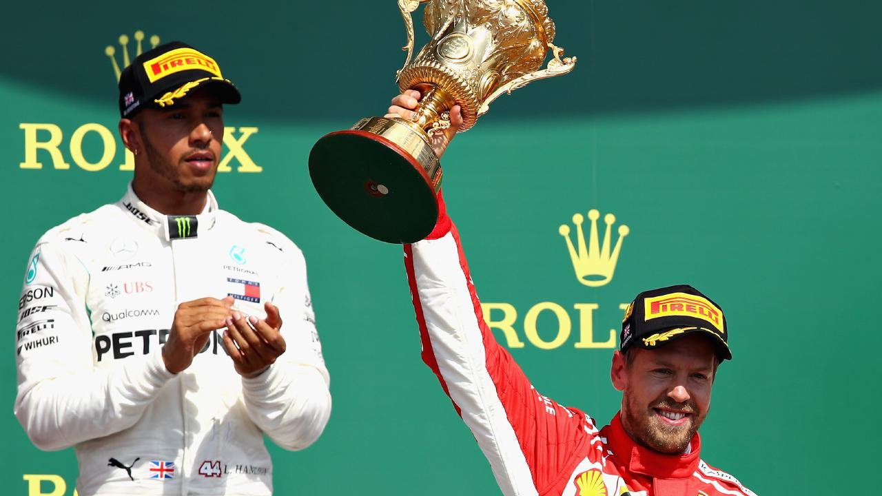 Race winner Sebastian Vettel celebrates on the podium as unimpressed second place finisher Lewis Hamilton looks on. Picture: Getty