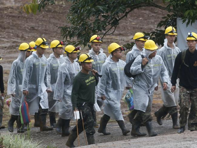Rescuers walk toward the entrance to the cave complex where five Thai soccer team members are still trapped. Picture: AP Photo/Sakchai Lalit