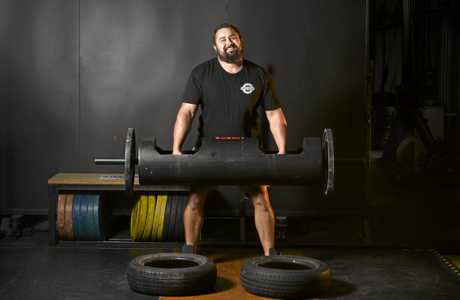 NOW OPEN: Strongman Kyle Greene , one of the owners aof a new gym at Blacksoil, lifting a 90kg 'tree'.