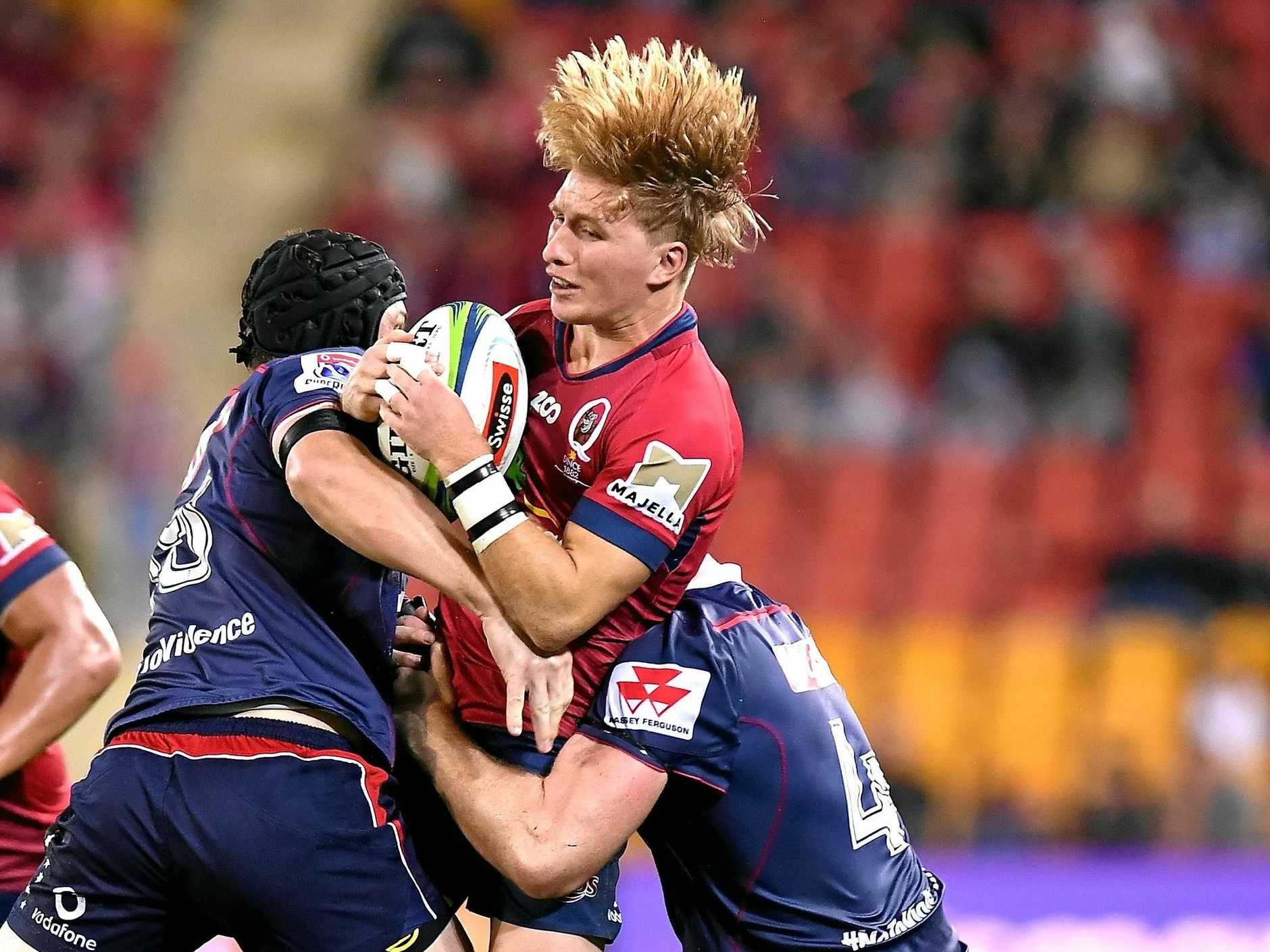 Tate McDermott cops a heavy tackle from the Rebels at Suncorp Stadium last Friday. Picture: Bradley Kanaris/Getty Images