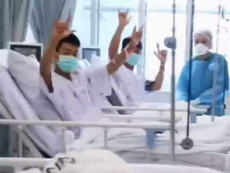 The rescued boys smile and wave at their parents through a glass partition. Picture: Twitter