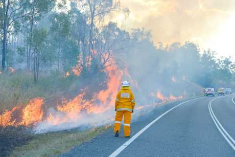 A Rural Fire Service volunteer burns off dry grass beside Gladstone Monto Rd.