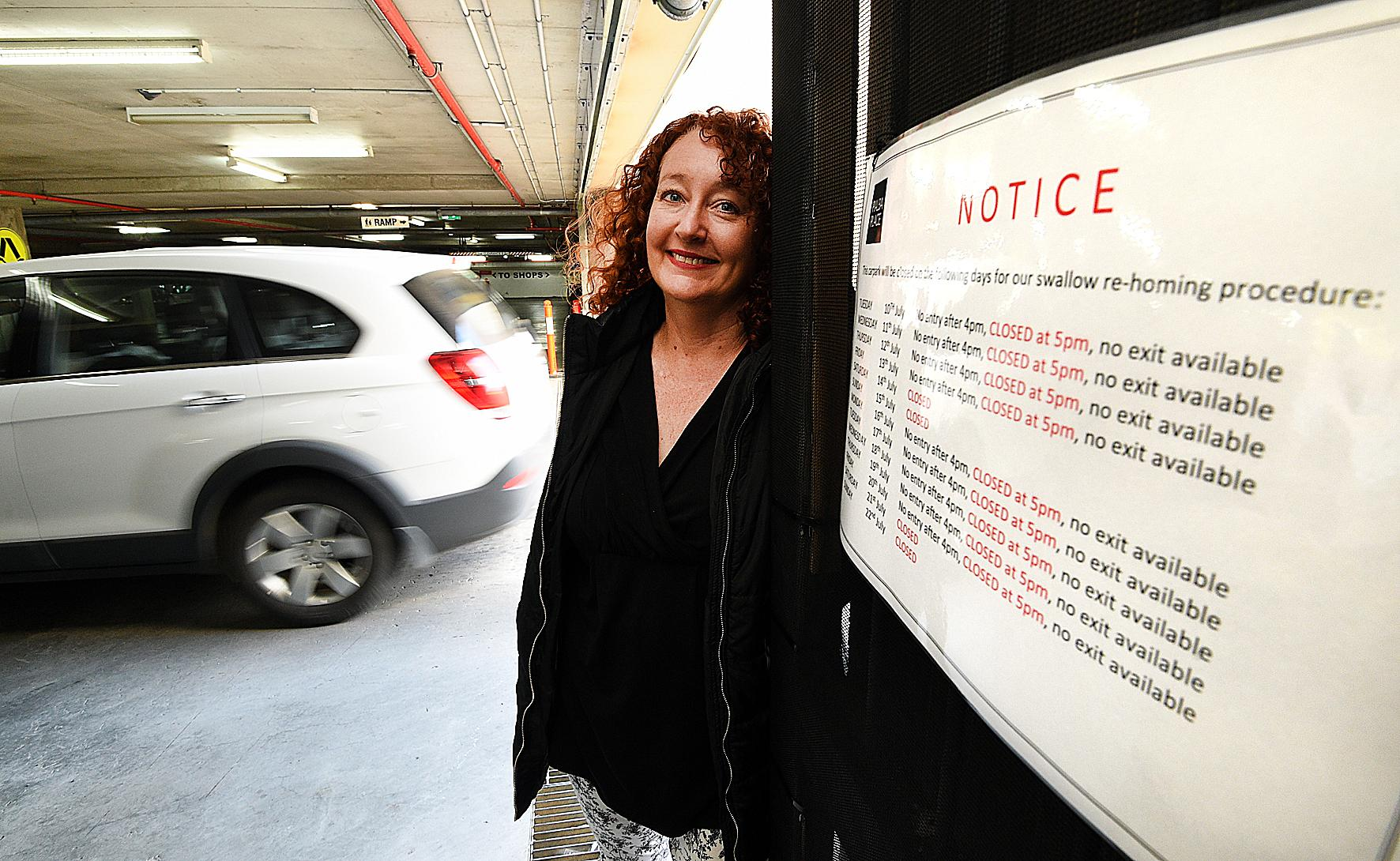 HARD TO SWALLOW: Pialba Place centre manager Rachel Mackey shows the notice advising shoppers the gate to the underground car park will close three hours earlier each day as part of the centre's swallow lock-out.