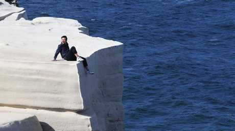 Idiots, they're everywhere. Here's one at Wedding Cake Rock in Sydney. (Pic: John Feder/The Australian)