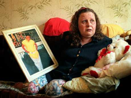 Barbara Phillips with a picture of her murdered daughter and the girl's teddy bear.