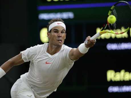 Rafael Nadal of Spain returns a ball to Novak Djokovic