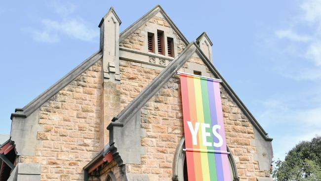 Trinity Uniting Church hangs a large rainbow-coloured Yes banner to support gay marriage. Picture: AAP Image/Morgan Sette