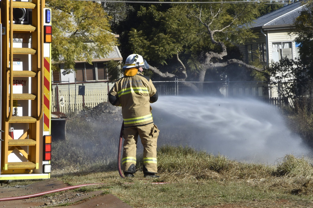 QFES firefighters extinguish a grass fire on a vacant bloke on the corner of Perth and Ruthven Street. July 2018