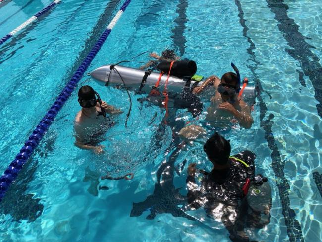 Divers test the device in a pool in Los Angeles. Picture: Elon Musk/ Supplied