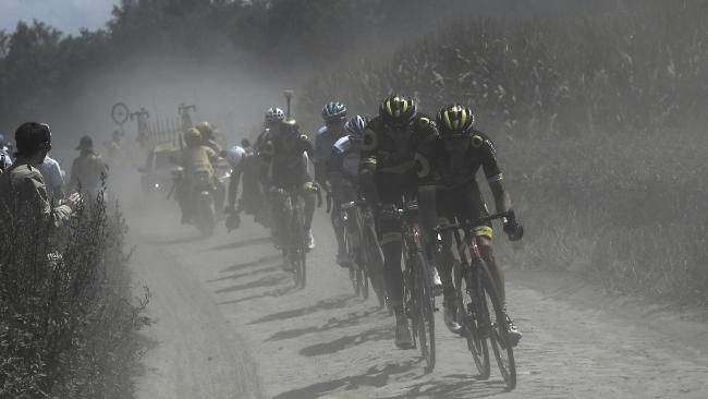 A nine-men breakaway rides in a cloud of dust on a cobblestone section of the ninth stage. Picture: AP
