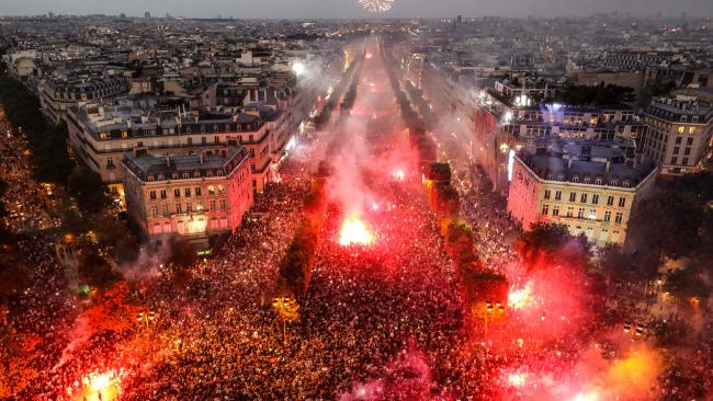 TOPSHOT - This picture taken from the top of the Arch of Triumph (Arc de Triomphe) on July 15, 2018 shows people lighting flares as they celebrate after France won the Russia 2018 World Cup final football match against Croatia, on the Champs-Elysees avenue in Paris. / AFP PHOTO / Ludovic MARIN
