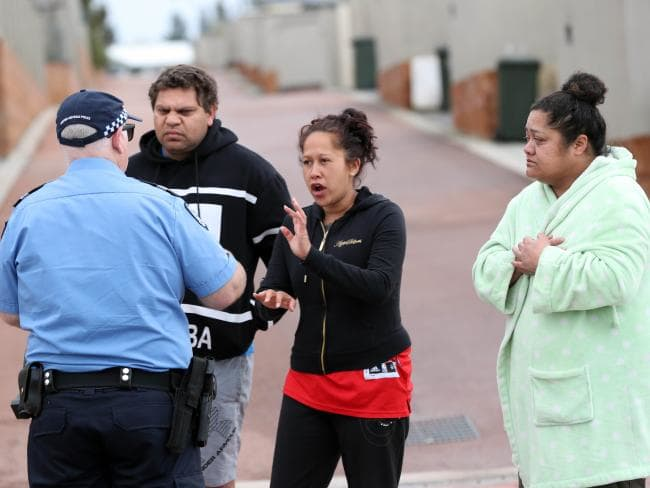 "People speak to police outside the house where the crime scene was described as ""complex and horrific"". Picture: AAP"