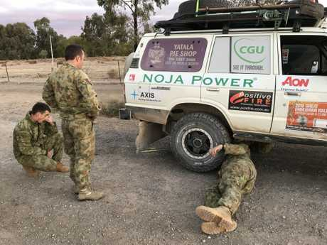 Members of the Australian Army 7th Combat Service Support Battalion inspect the damaged vehicle of the Canetoad Cruisers.