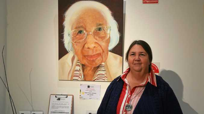 LOCAL TALENT: Sue Harm with the portrait she painted of Lena Kane hanging at Gayndah Art Gallery.