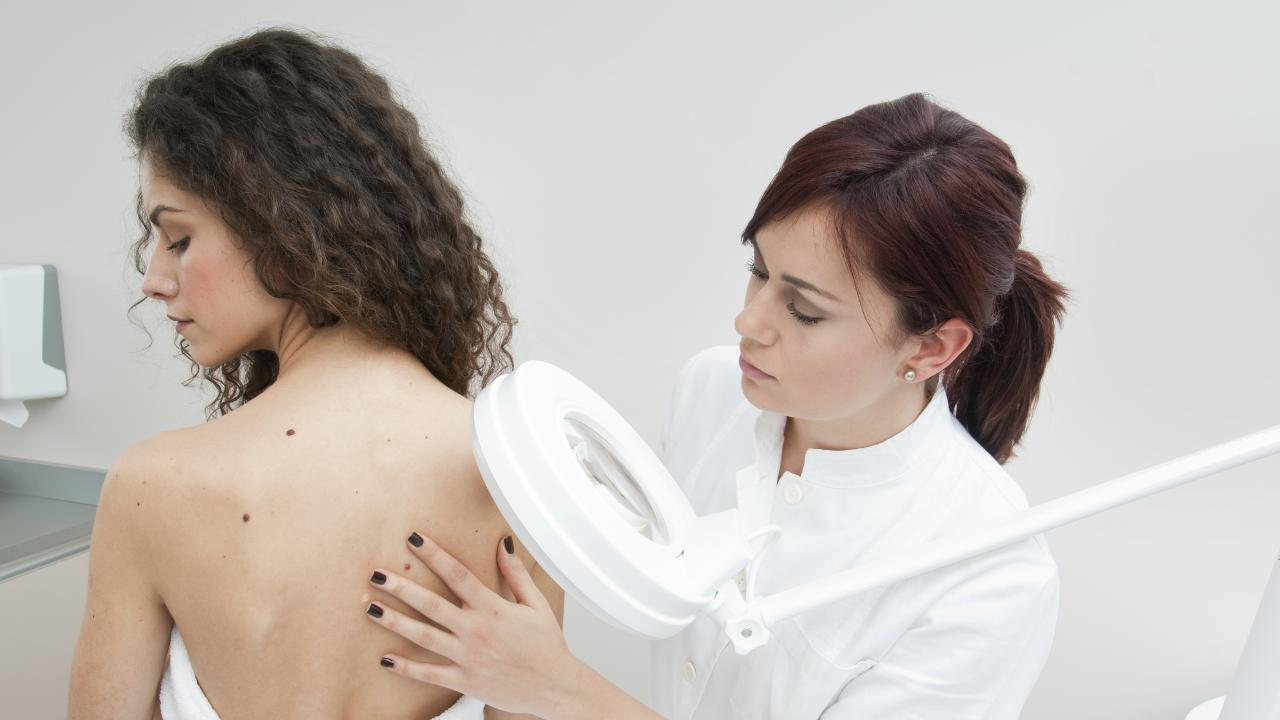 A doctor inspecting a woman's skin for melanomas.