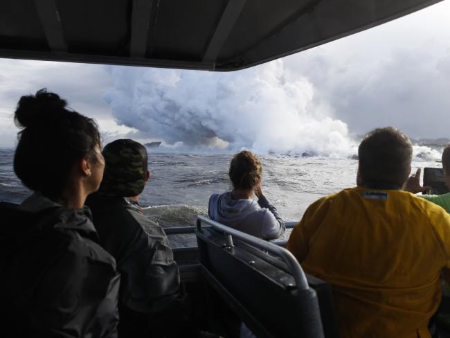 People watch a plume of steam as lava enters the ocean near Pahoa, Hawaii, in May. Picture: AP