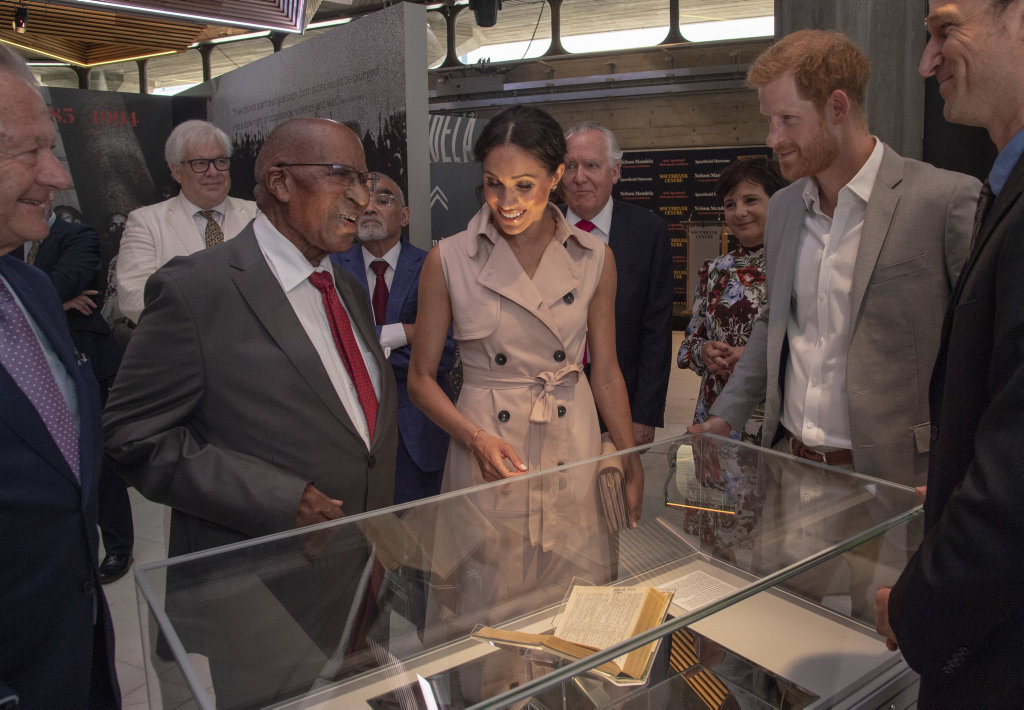 Prince Harry and Meghan, the Duchess of Sussex, look at a Shakespeare book favoured by prisoners on Robben Island with Andrew Miangeni, who was in prison with Nelson Mandela, at the launch of the Nelson Mandela Centenary Exhibition, marking the 100th anniversary of anti-apartheid leader's birth.