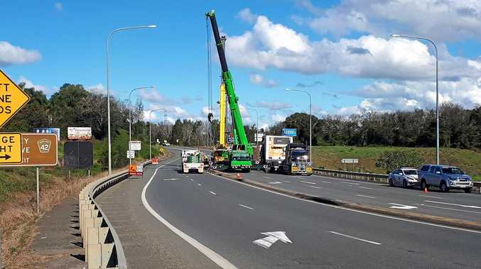 Cranes work to readjust the wide load which collided with the Mary Valley Rd overpass on the Bruce Highway last week.