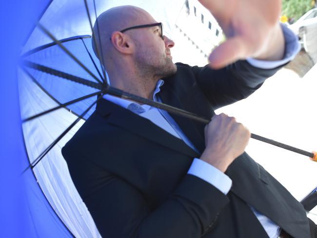 Dragi Stojanovski, Snezana's husband, hides behind an umbrella as he leaves court. Picture: Nicole Garmston