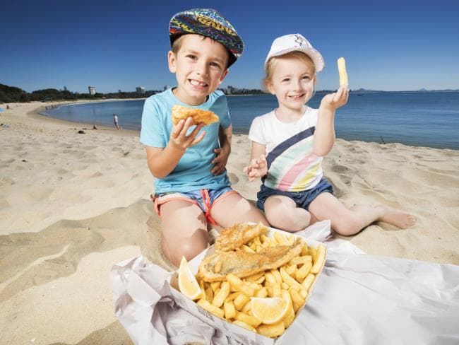 Blake Tamati, 5, from Buderim enjoys a spread of fish and chips from Fisheries on the Spit with little sister Stevie, 3, on the beach at Mooloolaba. Picture: Lachie Millard