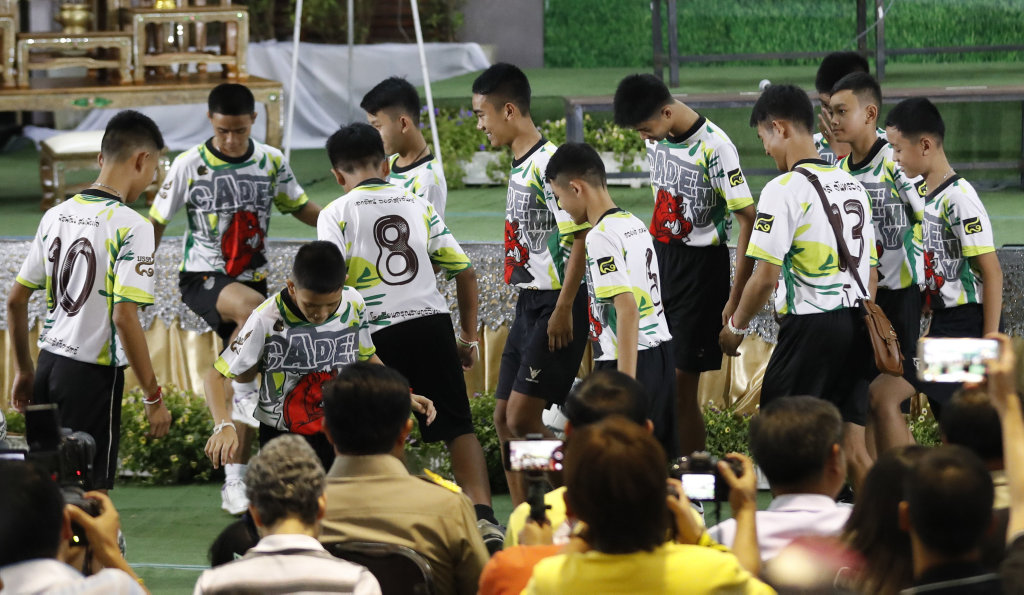 Members of the rescued soccer team and their coach dribble a few soccer balls before a press conference discussing their experience in the cave in Chiang Rai, northern Thailand.