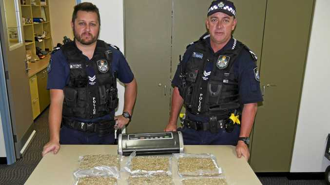 Arresting officer Senior Constable Dean Perz and Senior Constable Tony Parkinson with the 3.1 kilograms of cannabis seized in a drug bust this morning.