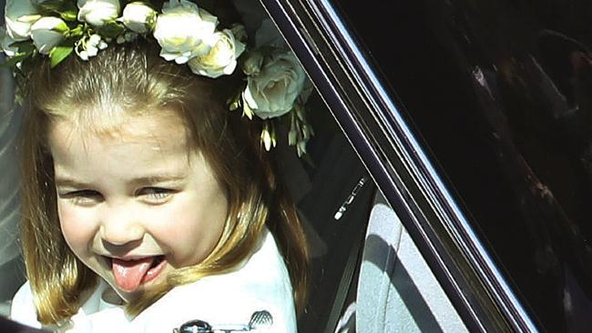 Princess Charlotte sticks out her tongue as she rides in a car to the wedding ceremony of Prince Harry and Meghan Markle. Picture: AP