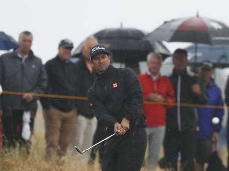 Adam Scott chips onto the green on the 15th. Picture: AP