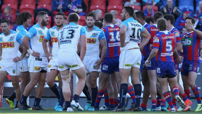 Knights players celebrate a try as dejected Titans look on. Photo: Getty Images