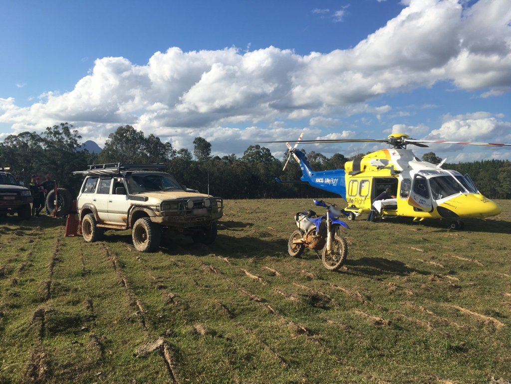 A rescue helicopter lands in a clearing near forestry where a motorbike rider was injured at Beerburrum.