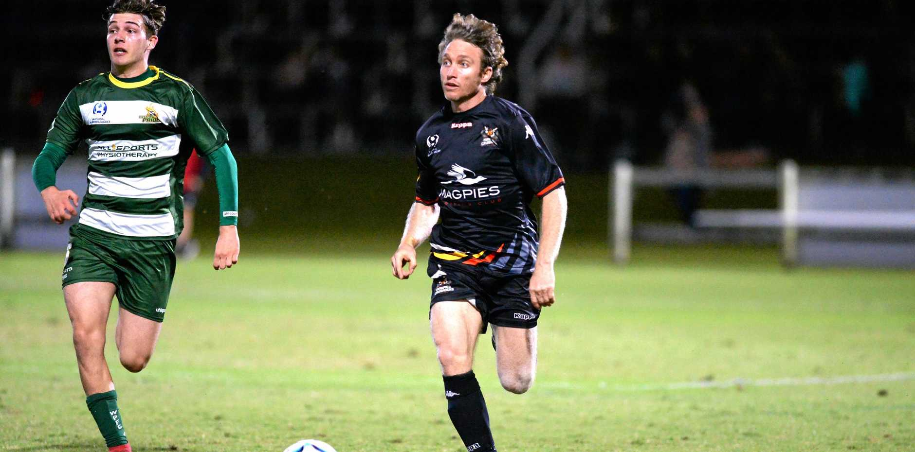 Magpies Crusaders' Allen Jackson is pursued by a Western Pride player in the NPL Queensland Round Four catch-up match at Sologinkin Oval, Mackay, on Saturday.