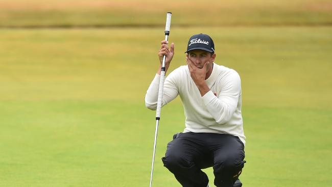 Australia's Adam Scott lines up a putt on the 18th