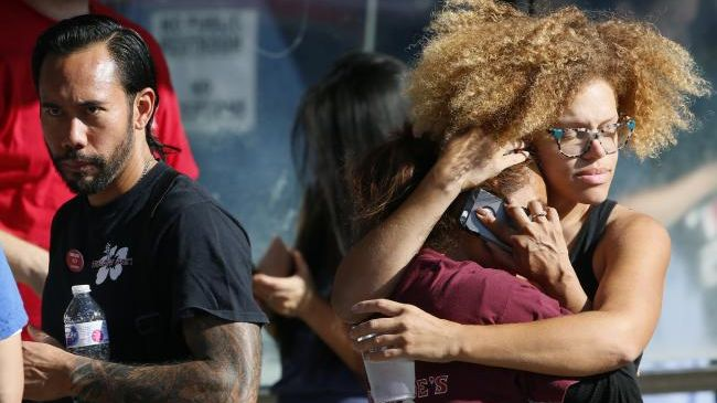 Trader Joe's supermarket employees hug after being evacuated by police after a gunman barricaded himself inside the store in Los Angeles. Picture: AP Photo/Damian Dovarganes