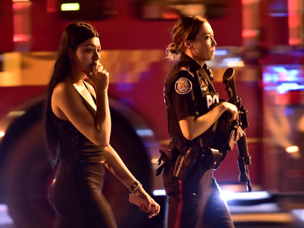 A police officer escorts a civilian away from the scene of a shooting, Sunday, July 22, 2018, in Toronto. Picture: AP
