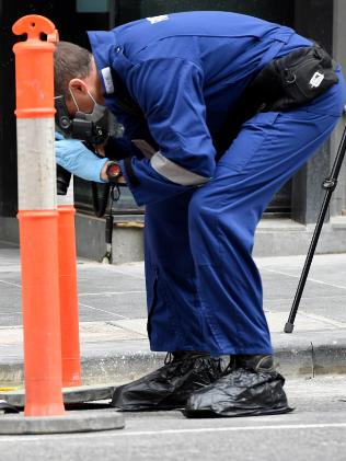 Forensic investigators search for evidence outside the EQ Tower. Picture: Nicole Garmston