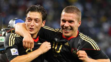 Mesut Oezil and Lukas Podolski of Germany celebrate victory following the 2010 FIFA World Cup Quarter Final match between Argentina and Germany.