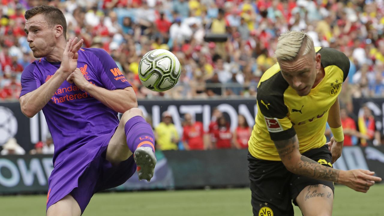 Liverpool's Andrew Robertson blocks a header by Borussia Dortmund's Marius Wolf.
