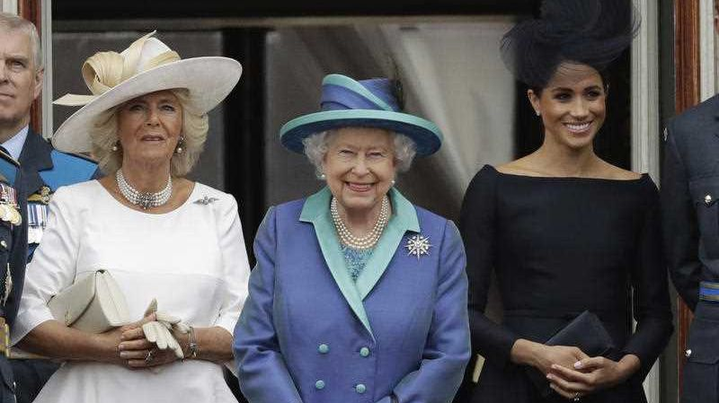 Britain's Queen Elizabeth II, Camilla the Duchess of Cornwall, left, and Meghan the Duchess of Sussex watch a flypast of Royal Air Force aircraft pass over Buckingham Palace in London, Tuesday, July 10, 2018. Various events were held Tuesday to mark the centenary of the RAF.