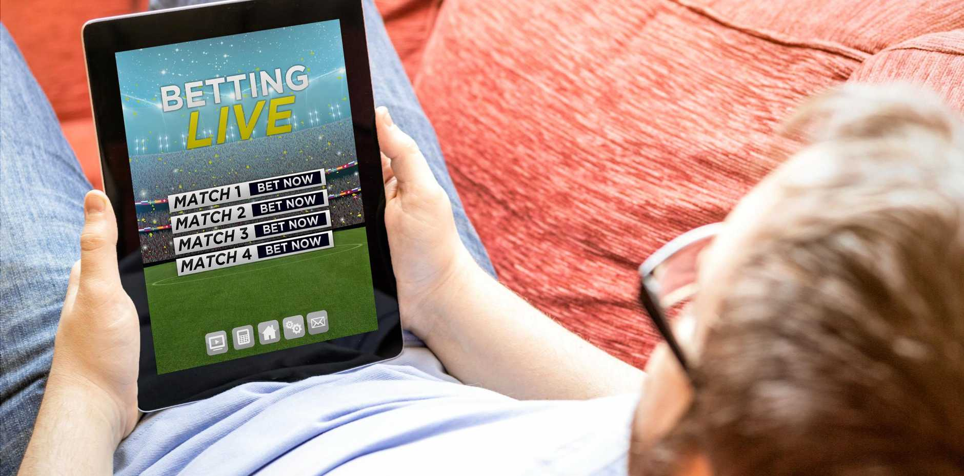 Man betting online on a tablet.