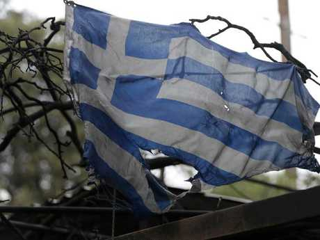 A tattered and charred Greek national flag hangs from a burnt-out house in Mati east of Athens. Picture: AP