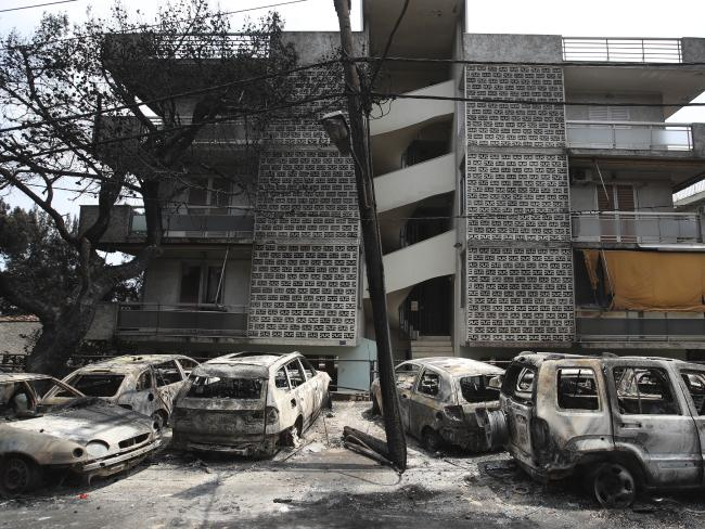 Burnt-out cars stand outside an apartment block in Mati east of Athens. Picture: AP