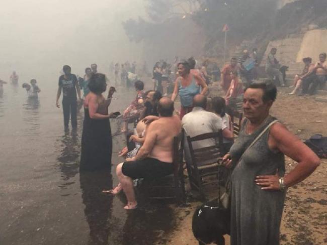 People take refuge from Greece fires in Argyris Akti, Nea Makri, Greece. Picture: Kalogerikos Nikos