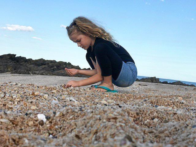 Ava Sealby collecting shells on the family road trip.