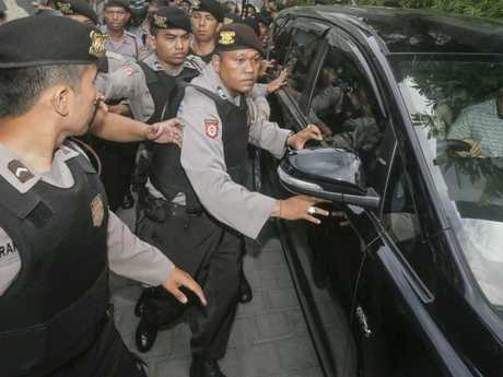 Several police in Indonesia escort Schapelle Corby's car out of her home. Picture: Johannes Christo