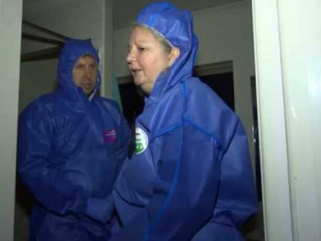 Torso killer Lindy Williams, clad in a forensic suit, shows police the scene of the crime after her arrest.