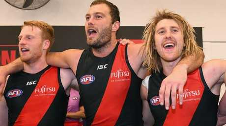 Happy Essendon players Aaron Francis, Tom Bellchambers and Dyson Heppell sing the team song after the win. Picture: Quinn Rooney/Getty