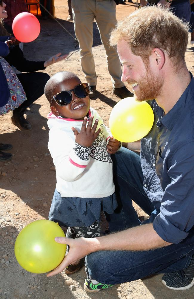 Prince Harry, Duke of Sussex plays with children holding balloons in Leribe, Lesotho. Picture: Getty