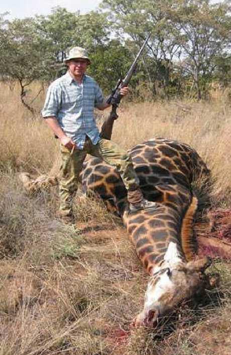 Gold Coast businessman Vitali Roesch posing with an endangered giraffe.