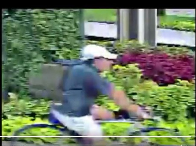 Grainy CCTV footage shows the suspect, wearing a T-shirt, shorts, cap and olive-green backpack stalking his victim on bike. Picture: Houston Police Department