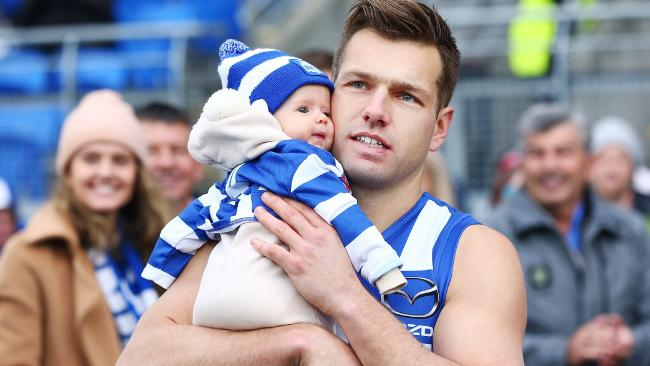 Shaun Higgins walks out with his child for his 200th match.
